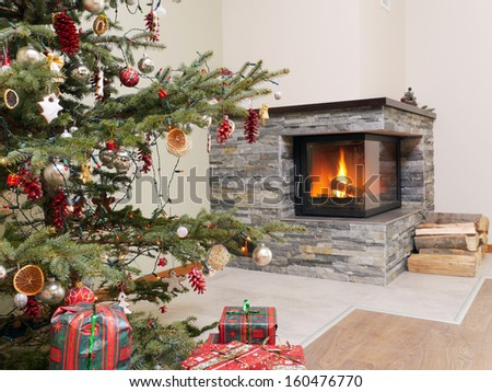 Christmas tree with lots of christmas presents by the lit fireplace - stock photo
