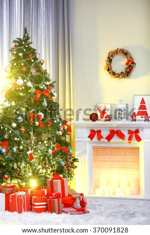Christmas tree with presents near the fireplace in a room
