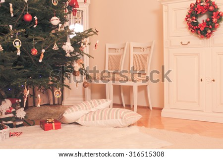 Christmas tree with presents underneath  of Santa Claus and two pillows lying along - stock photo