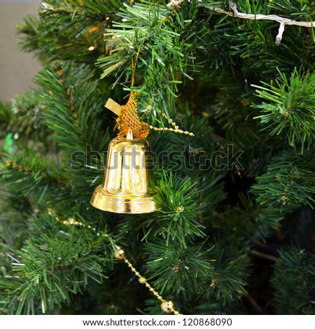 Christmas tree with some decorations, Golden bell hanging on a green spruce branch