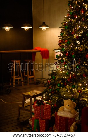 Christmas tree with toys, gifts and light bulbs in living room in the evening