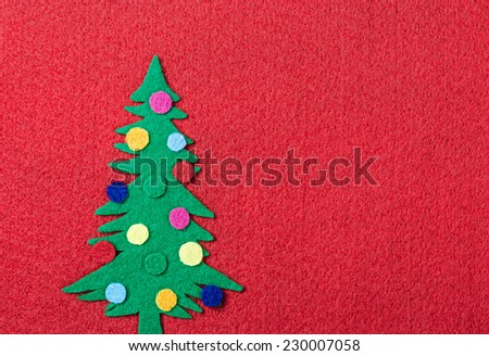 Christmas tree with toys made of felt on a red background - stock photo