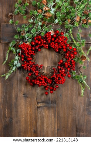 Christmas tree wreath from red berries over rustic wooden background. Festive decoration