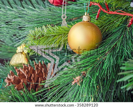 Christmas tree yellow ornaments, globe hanging, snow flake, green tree, firs with cones, close up. - stock photo