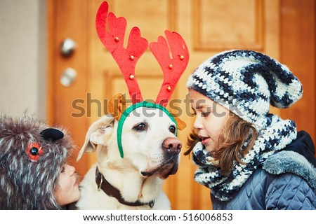 Christmas walk with dog. Two girl are going out with labrador retriever dressed as a Christmas reindeer.