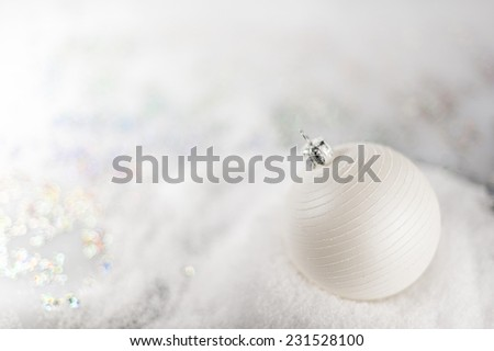 Christmas white bauble on the snow with soft light blurred background, very shallow DOF. - stock photo
