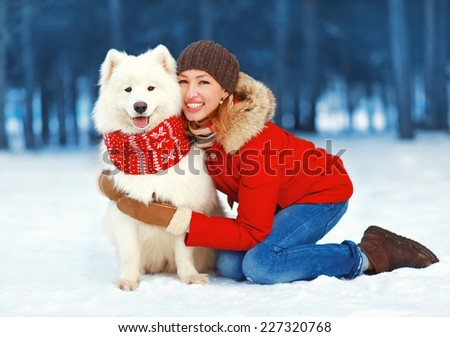 Christmas, winter and people concept - happy pretty woman having fun with white Samoyed dog outdoors in winter day - stock photo