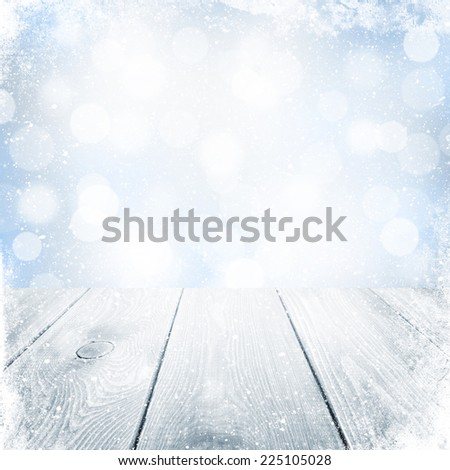 Christmas winter background with snow, wooden table and blurred bokeh - stock photo