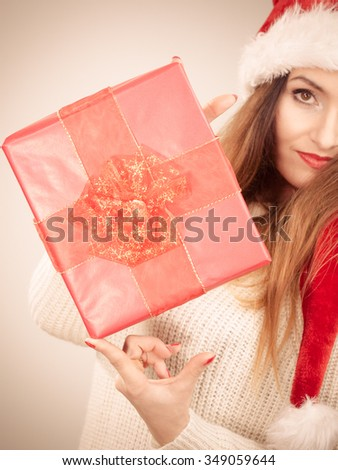 Christmas winter happiness concept. Latin woman wearing santa helper hat holding present red gift box