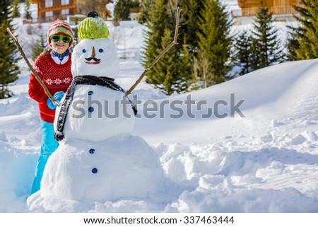 Christmas, Winter holiday, happy girl playing with snowman - stock photo
