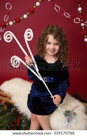 Christmas, Winter Holiday themed setup: beautiful child ornaments and decorations on red background - stock photo