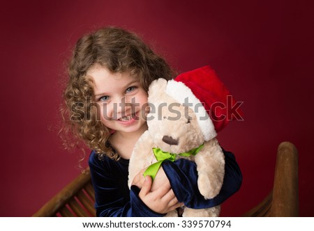 Christmas, Winter Holiday themed setup: beautiful child with stuffed bear toy in santa hat on red background - stock photo