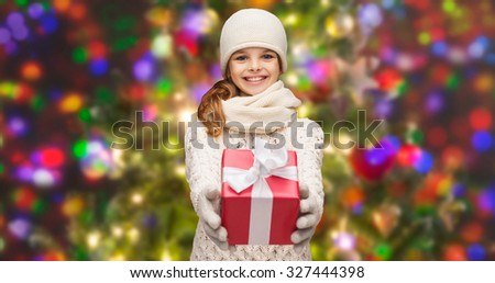 christmas, winter, holidays and childhood concept - smiling girl in hat, muffler and gloves with gift box over glitter or lights background