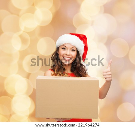 christmas, winter holidays, delivery, gesture and people concept - smiling woman in santa helper hat with parcel box showing thumbs up over beige lights background - stock photo