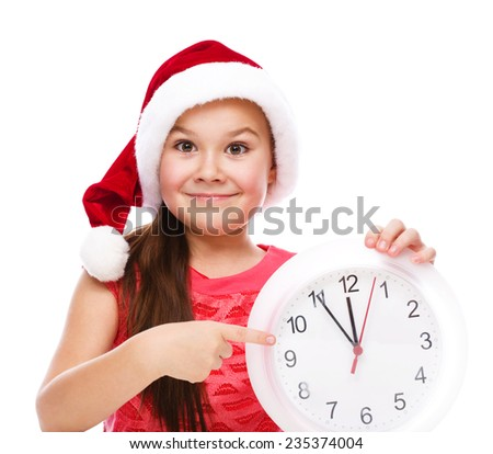 Christmas, winter, time and people concept - girl in santa helper hat with clock, isolated over white - stock photo