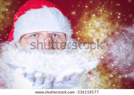 Christmas winter with Santa Claus blowing magical glitter, stardust. Red background. New Year.