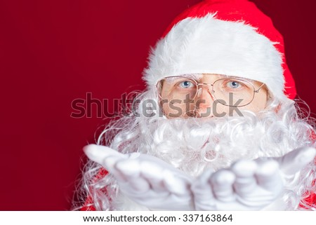 Christmas winter with Santa Claus blowing magical glitter, stardust. Red background. New Year. Copy space