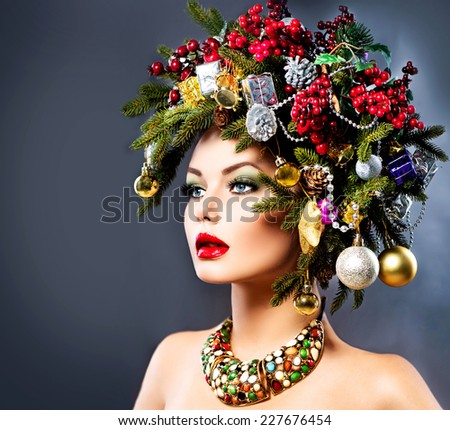 Christmas Winter Woman. Beautiful New Year and Christmas Tree Holiday Hairstyle and Make up. Beauty Fashion Model Girl dark Background. Creative Hair style decorated with Baubles  - stock photo