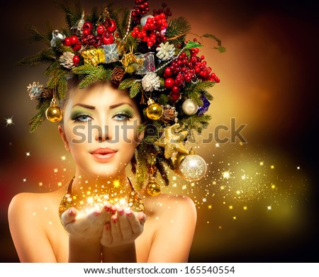 Christmas Winter Woman with Miracle in Her Hand. Fairy. Beautiful New Year and Christmas Tree Holiday Hairstyle and Make up. Magic. Beauty Fashion Model Girl blowing Holiday Magic stars.  - stock photo