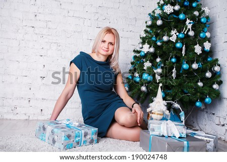 Christmas Winter Woman with Miracle in Her Hand. Fairy. Beautiful New Year and Christmas Tree Holiday Hairstyle and Makeup. Gift. Magic Girl. Beauty Fashion Model over Holiday Blurred Background.  - stock photo
