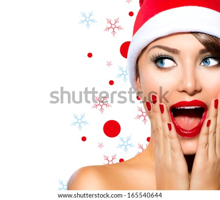 Christmas Woman. Beauty Model Girl in Santa Hat isolated on White Background. Funny Laughing Surprised Woman Portrait. Open Mouth. True Emotions. Red Lips and Manicure. Beautiful Holiday Makeup.  - stock photo