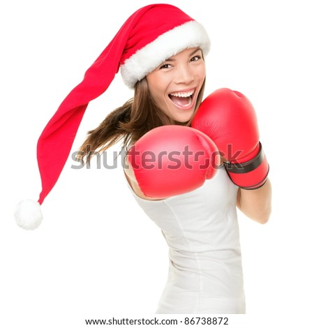 Christmas woman hitting wearing boxing gloves and red santa hat. Shopping boxing day or fitness concept. Beautiful fresh energy from asian caucasian female model isolated on white background. - stock photo