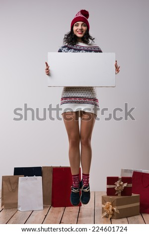 Christmas woman hold big white card copyspace. Winter knitted beanie hat. Full length. - stock photo