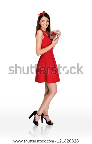 christmas woman holding a present wearing red dress - stock photo