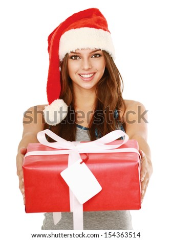 Christmas woman holding gift wearing Santa hat. Isolated on white background. - stock photo