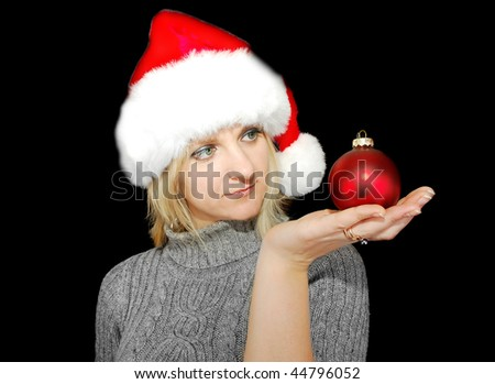 Christmas woman in red hat with ball decoration on the black background. Profile portrait.