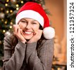 Christmas Woman in Santa Hat.Happy Smiling Girl Celebrating New Year at Home.Christmas Tree - stock photo