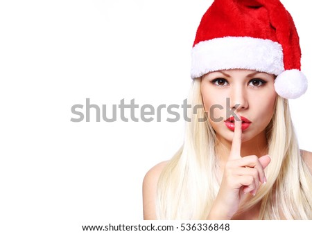 Christmas Woman. Sexy Blonde Girl in Santa Hat with finger on her red lips showing Hush, isolated