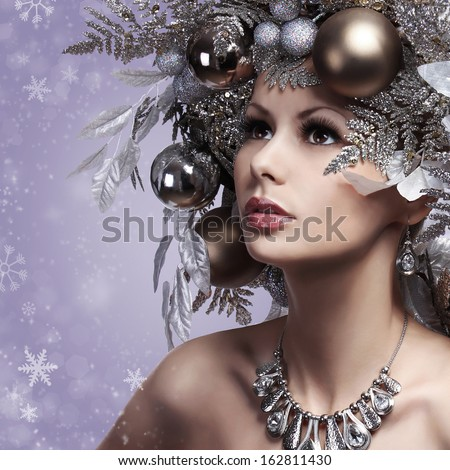 Christmas Woman with New Year Decorated Hairstyle. Snow Queen. Portrait of Fashion Girl with Silver and Gold Christmas Balls over Snowflakes background. Holiday Card - stock photo