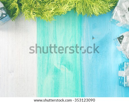Christmas wooden background with christmas tree decorations with a branch of thuja on green and blue pastel board. copy space for text - stock photo