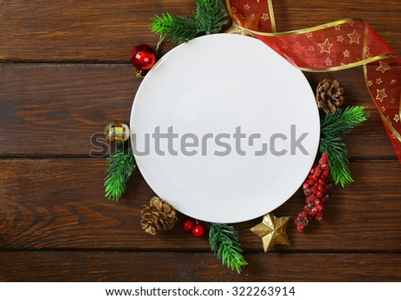 Christmas wooden background with fir branches, decoration and white plate - stock photo