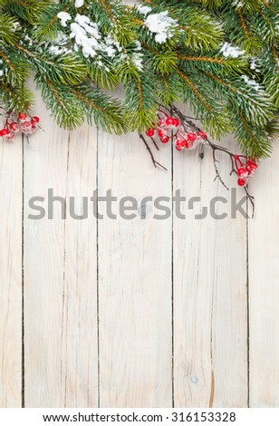 Christmas wooden background with fir tree and holly berry. View from above with copy space - stock photo