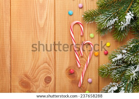 Christmas wooden background with snow fir tree and candies. View from above with copy space - stock photo