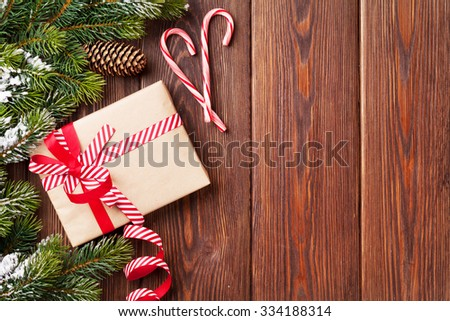 Christmas wooden background with snow fir tree and gift box. View with copy space - stock photo