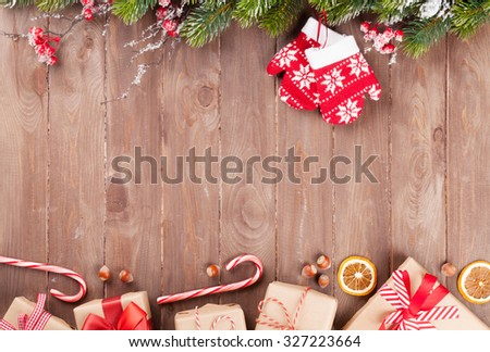 Christmas wooden background with snow fir tree and gift boxes. View with copy space - stock photo