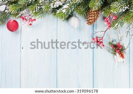 Christmas wooden background with snow fir tree and holiday decor - stock photo
