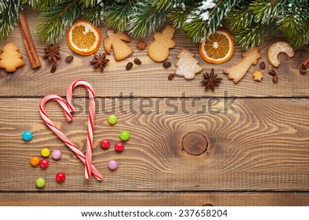 Christmas wooden background with snow fir tree, spices, gingerbread cookies and candies. View from above with copy space - stock photo