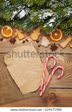 Christmas wooden background with snow fir tree, spices, gingerbread cookies and paper for copy space - stock photo