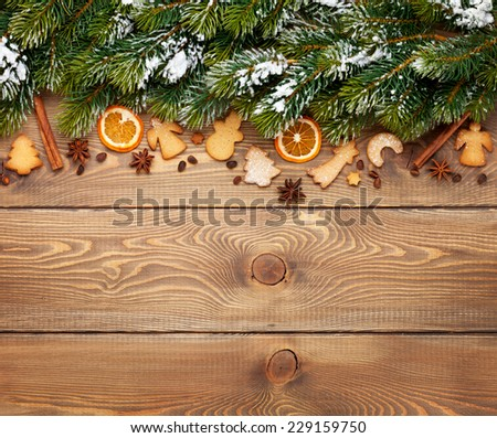Christmas wooden background with snow fir tree, spices, gingerbread cookies. View from above with copy space - stock photo