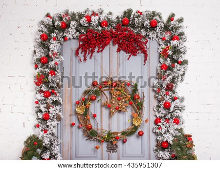 Christmas wooden door with fir branches an new year decoration.