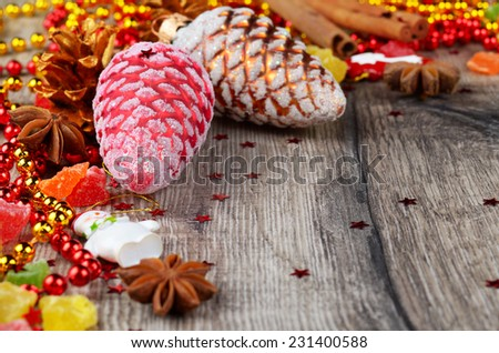 Christmas wooden table frame with baubles spices and candies - stock photo