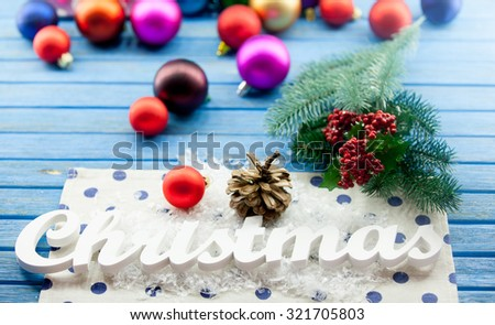Christmas word and toys on wooden background.