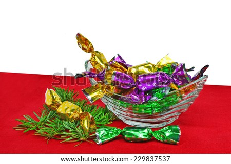 Christmas wrapped candies in glass bowl over red table cloth..
