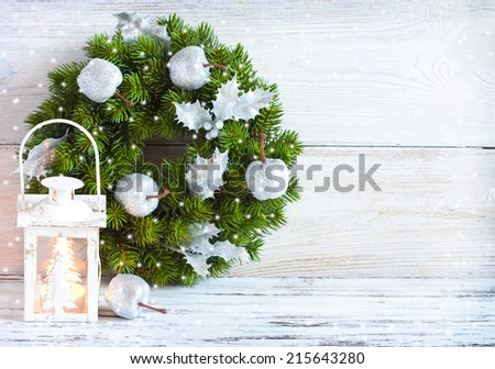 Christmas wreath and candle lantern on an old wooden background with copy space. - stock photo