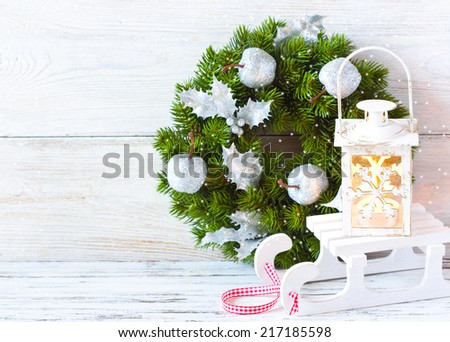 Christmas wreath and candle lantern with sledge lon an old wooden background with copy space. - stock photo