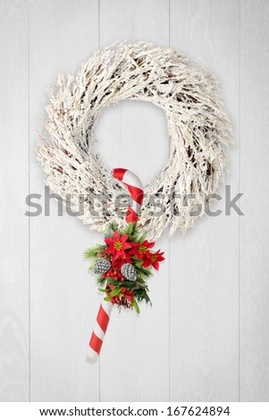 Christmas wreath  and cane on white wooden background. - stock photo